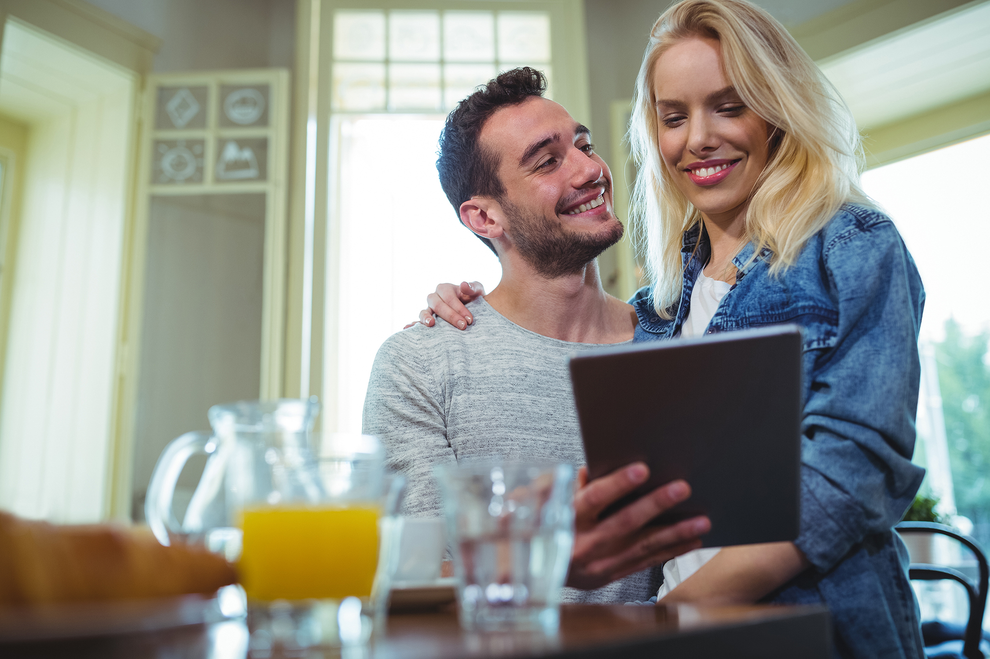 Couple sitting at table and using digital tablet in café